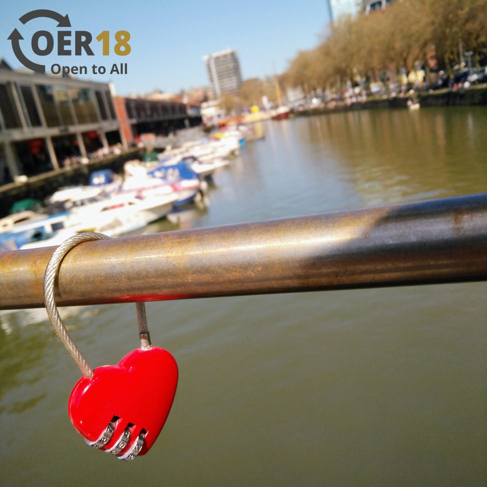 A heart shaped padlock attached to a bridge.